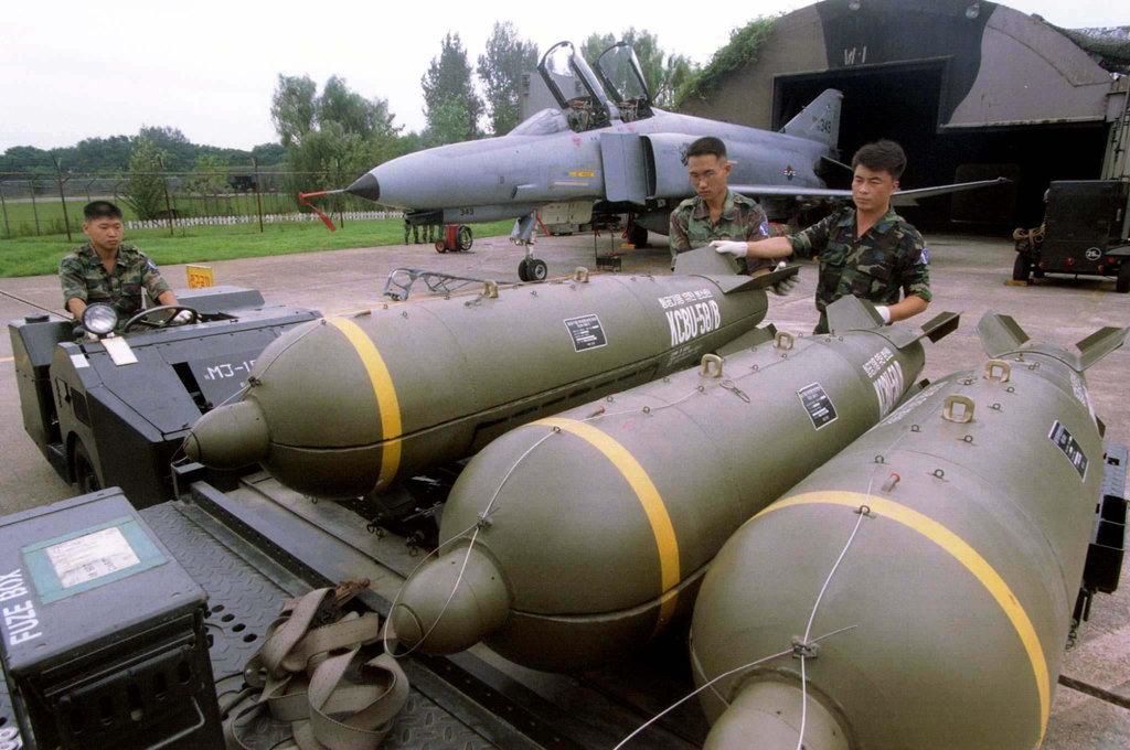 Miembros del círculo militar sureño se preparan para cargar bombas de racimo en un caza durante un ejercicio en una base aérea en Suwon, Sur de Corea.